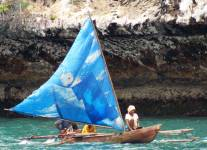 Papuan outrigger canoe under sail in Triton Bay